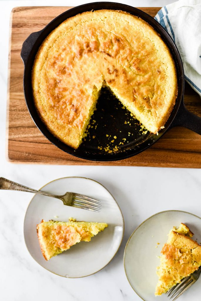 overhead of two plates with slices of cornbread beside cast iron skillet