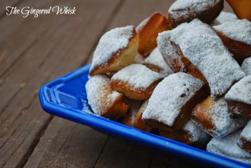 sourdough beignets piled up on blue platter