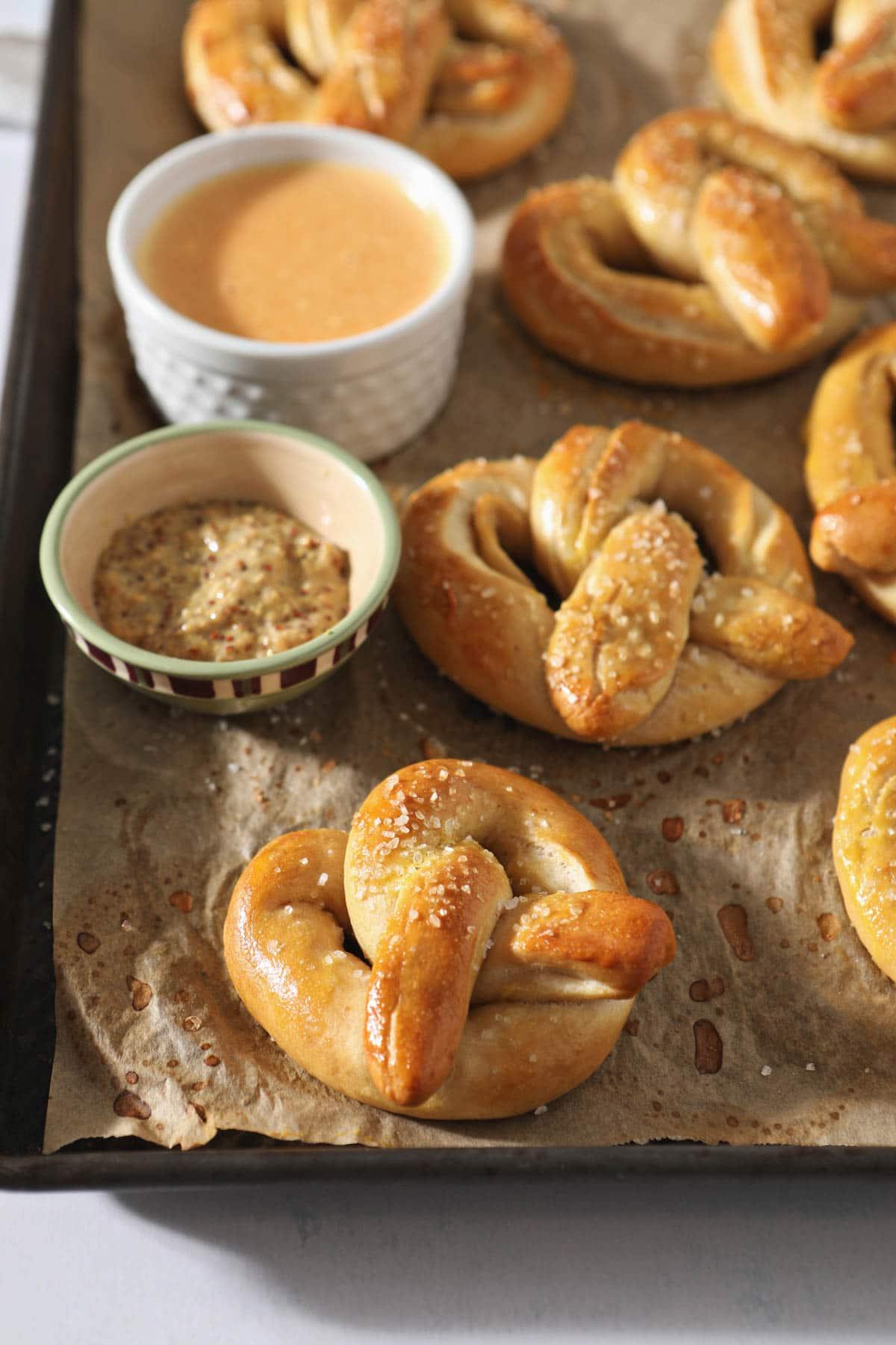 freshly baked pretzels beside honey mustard and cheese dip