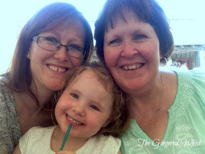 two women and a toddler smiling at the camera