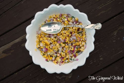 overhead view of corn salsa in white bowl with spoon on top