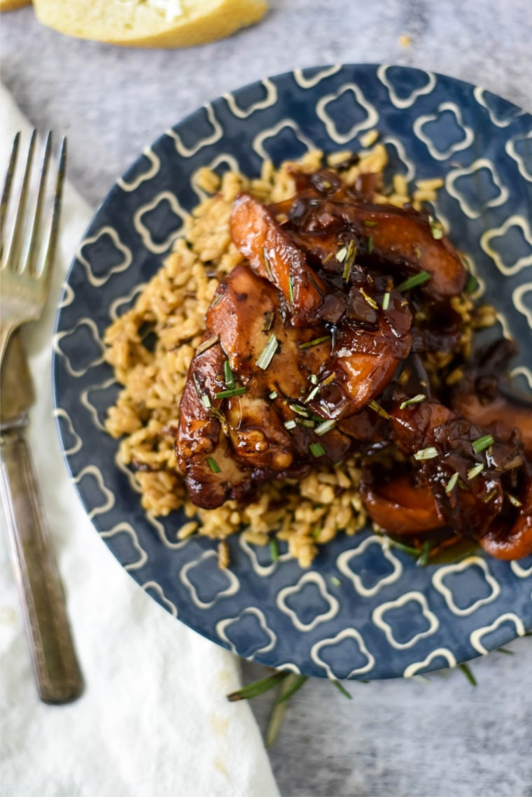 peach balsamic chicken with brown rice on blue plate