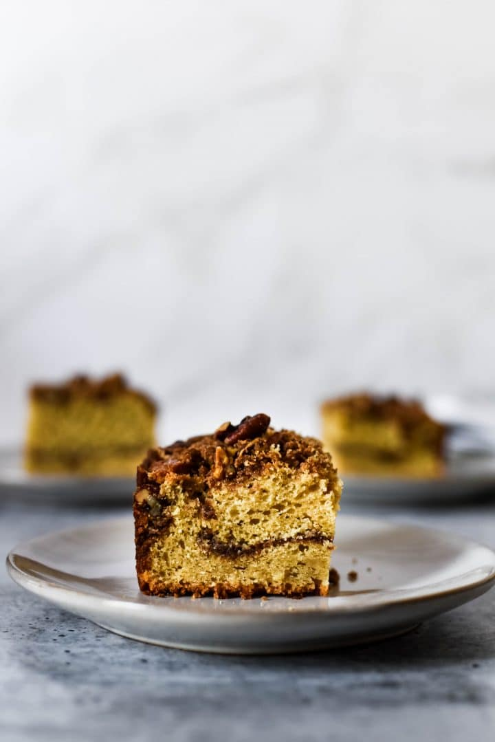 sourdough coffee cake on small grey plate with two slices in background