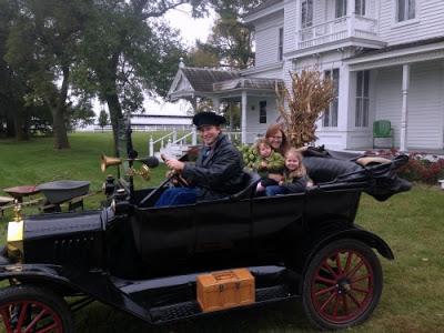 A man riding an old time car