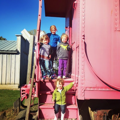 little girls standing on red train caboose