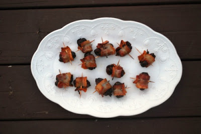 bacon wrapped dates on white platter