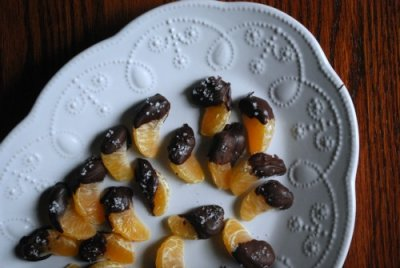 overhead view of oranges dipped in chocolate on white plate