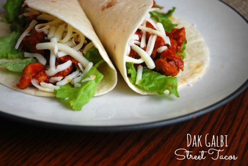 plate with two tortillas filled with dak galbi chicken, lettuce, and shredded mozzarella cheese