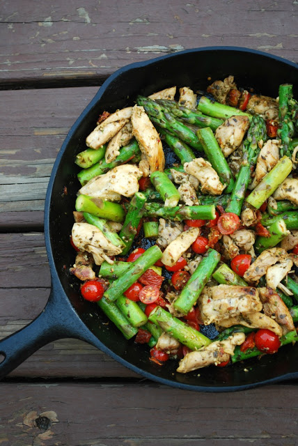 overhead view of cast iron skillet with chicken, tomatoes, and asparagus