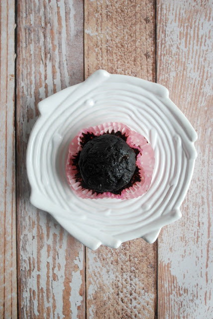 muffin in pink paper sitting on white plate
