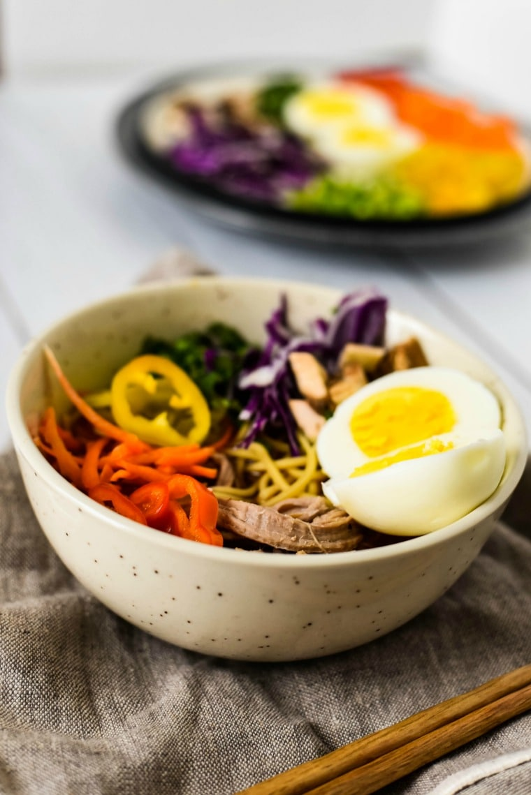 Close up of bowl of ramen with rainbow toppings
