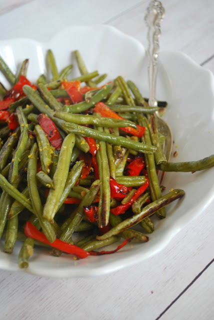 roasted green beans with red peppers in white serving bowl