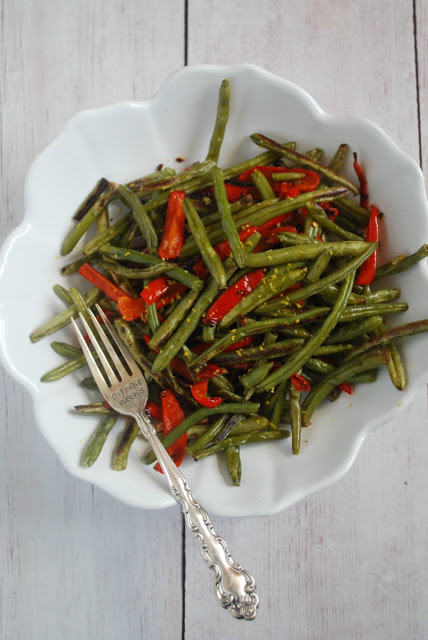 white bowl with green beans and red pepper strips