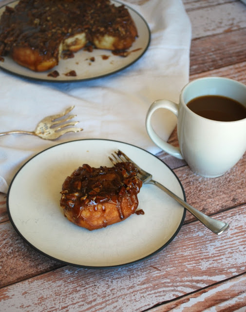 A plate of chocolate pecan sticky buns and a cup of coffee on a table, with a fork beside