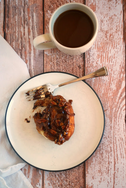 chocolate pecan sticky roll with cup of coffee