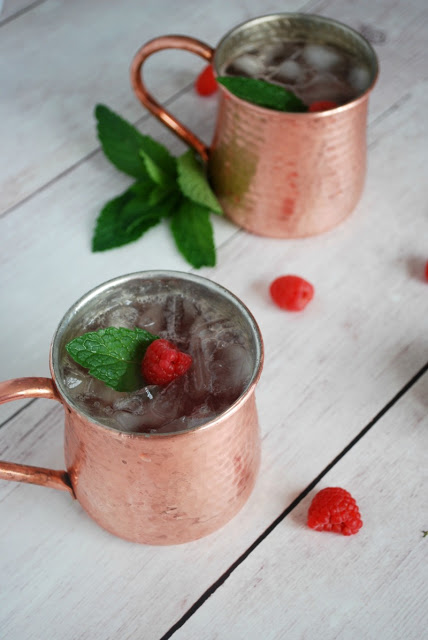 two moscow mule mugs with raspberry mules and mint