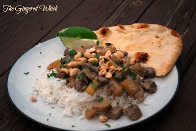 plate of white rice and beef curry with lime wedge and naan