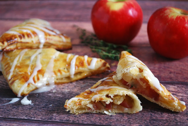 apple turnovers on wooden board with apple behind