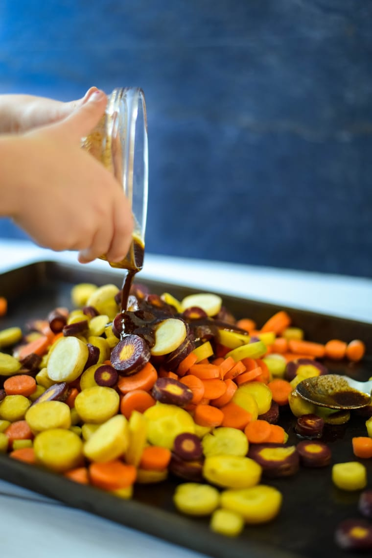 child pouring spices on rainbow carrots to roast