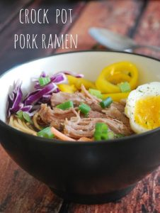 bowl of pork ramen with cabbage, peppers, and hard boiled egg