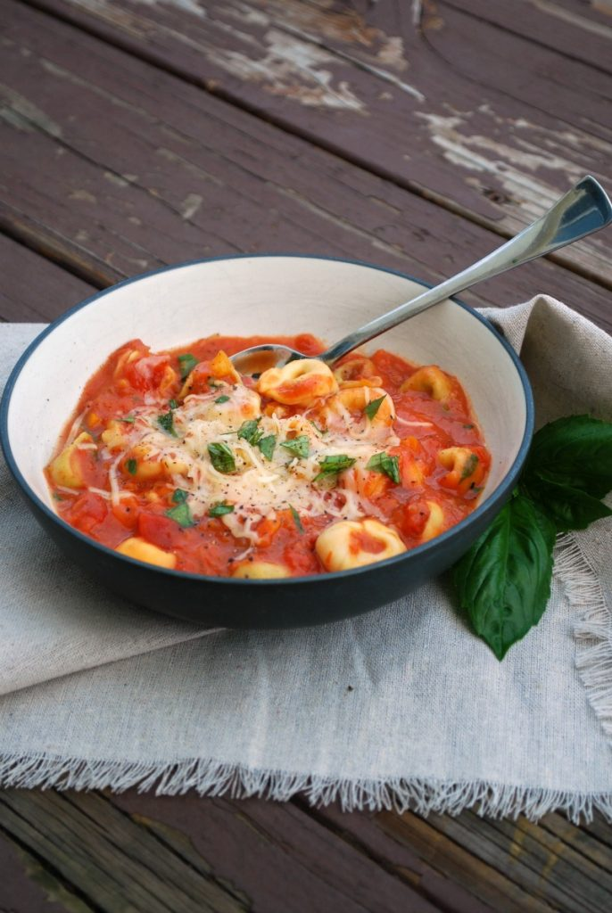 bowl of soup with tomatoes and cheese tortellini