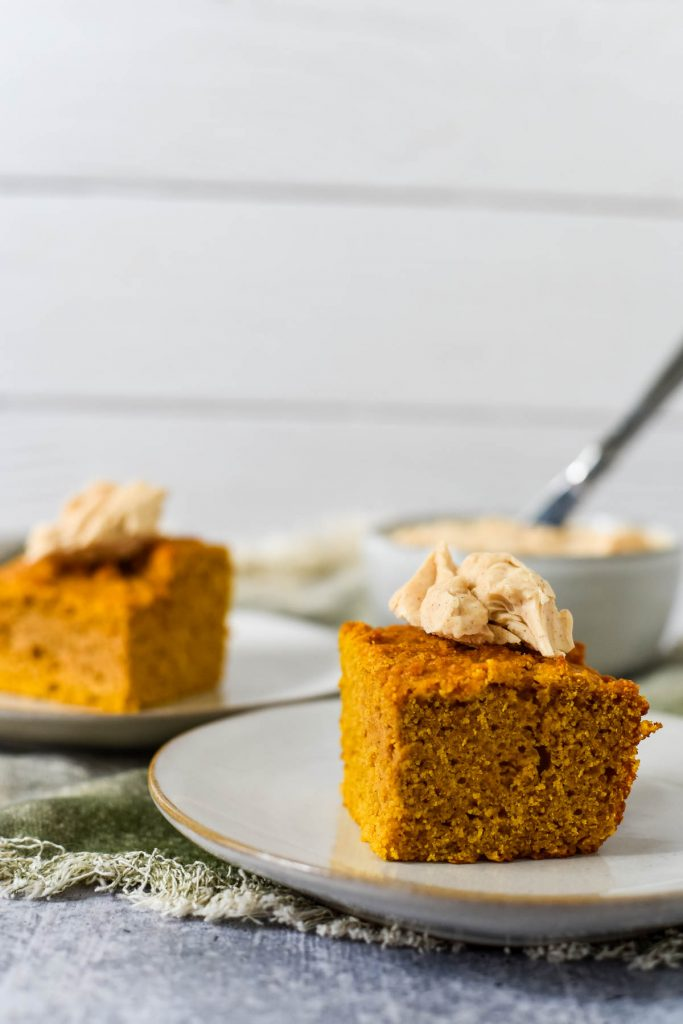 two pieces of pumpkin cornbread on plates with butter behind