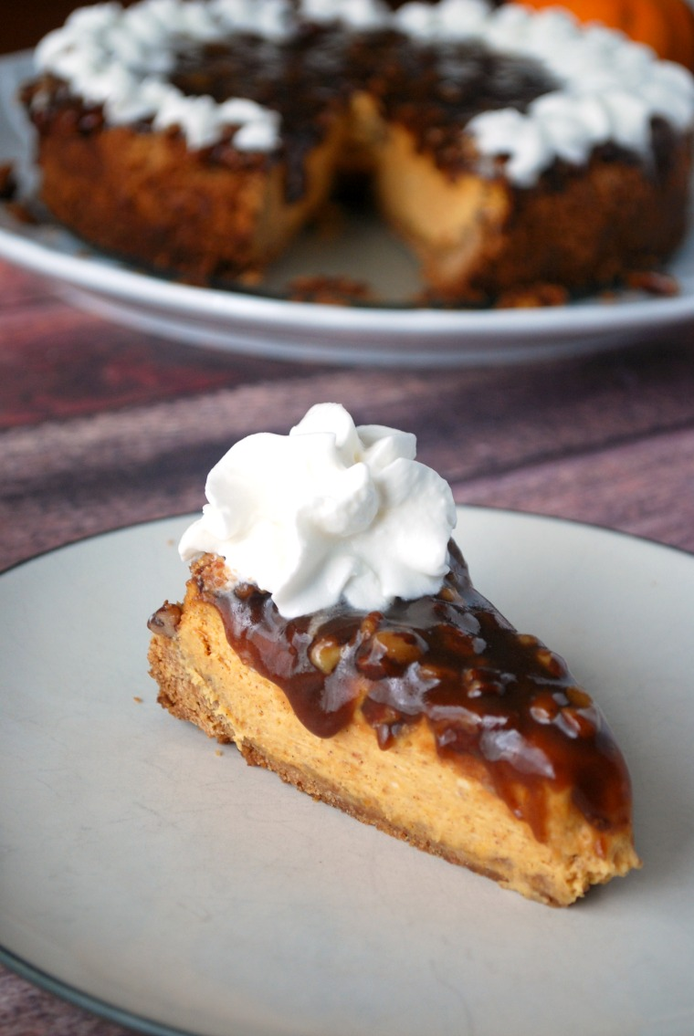 slice of pumpkin cheesecake with pecan topping and whipped cream on plate