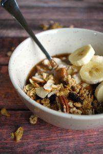 white bowl with yogurt, granola, and banana slices