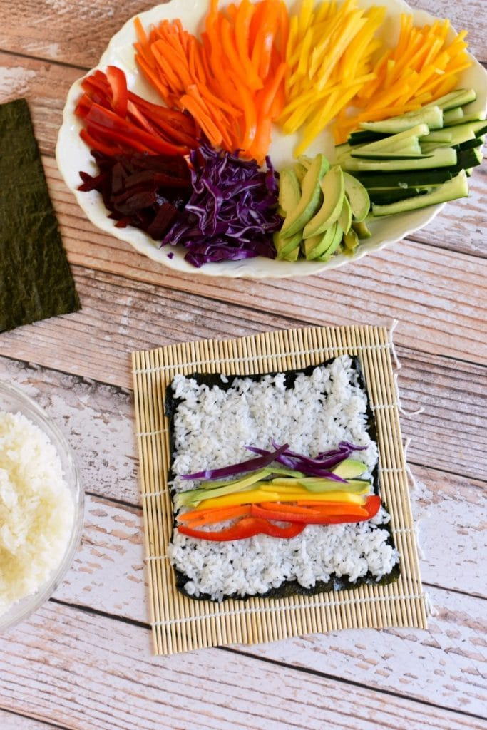 preparing rainbow vegetable sushi roll on bamboo mat