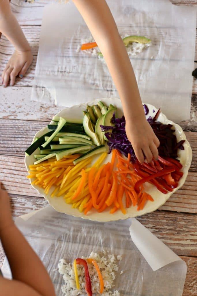 kids making rainbow sushi on rice paper