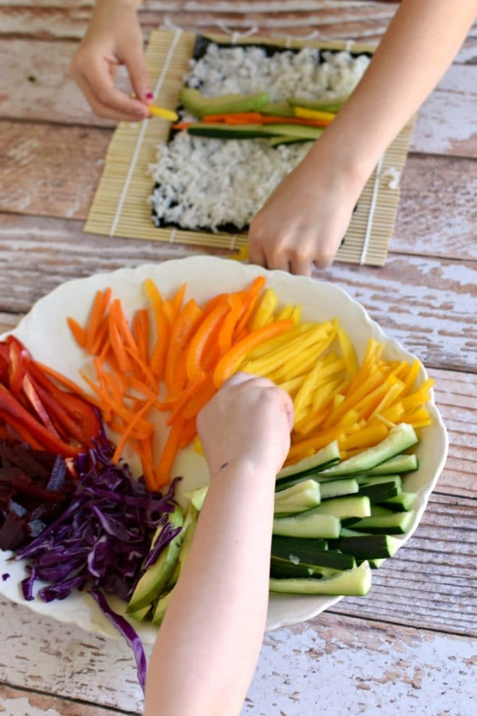 kids making sushi with rainbow vegetables on white platter