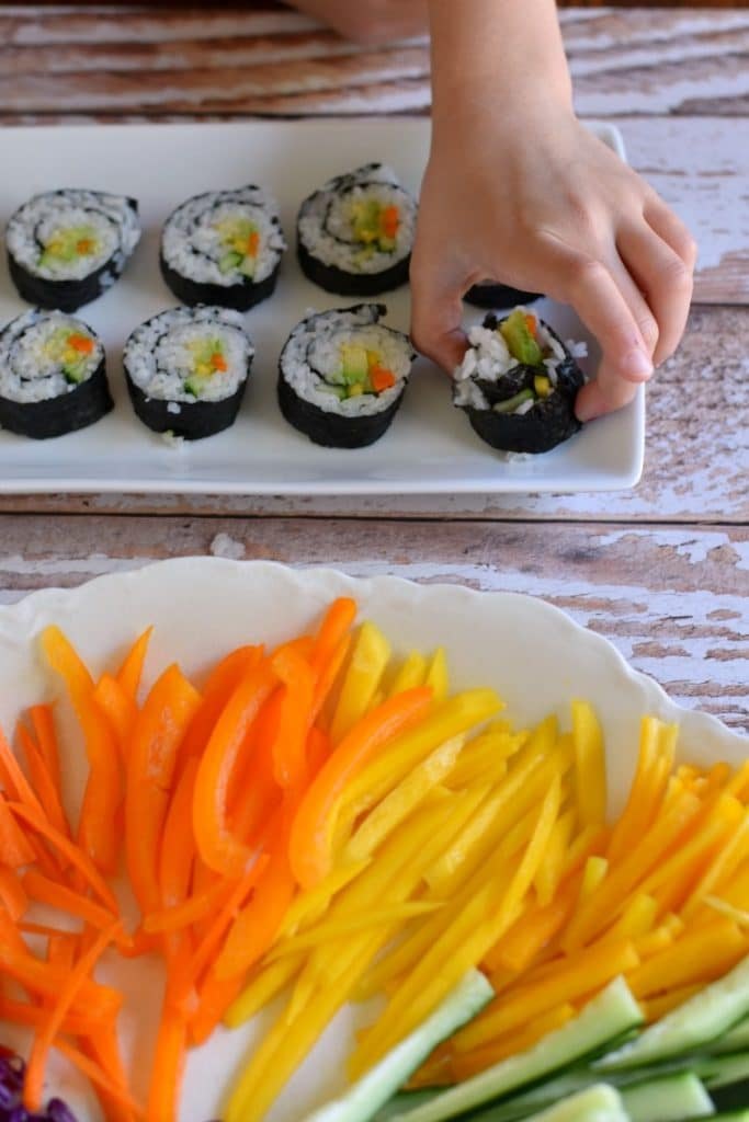 Kids eating rainbow veggie sushi