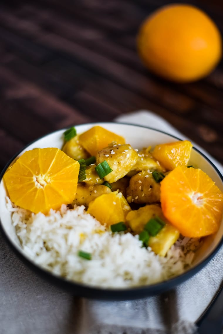 orange chicken in bowl with rice on wood background