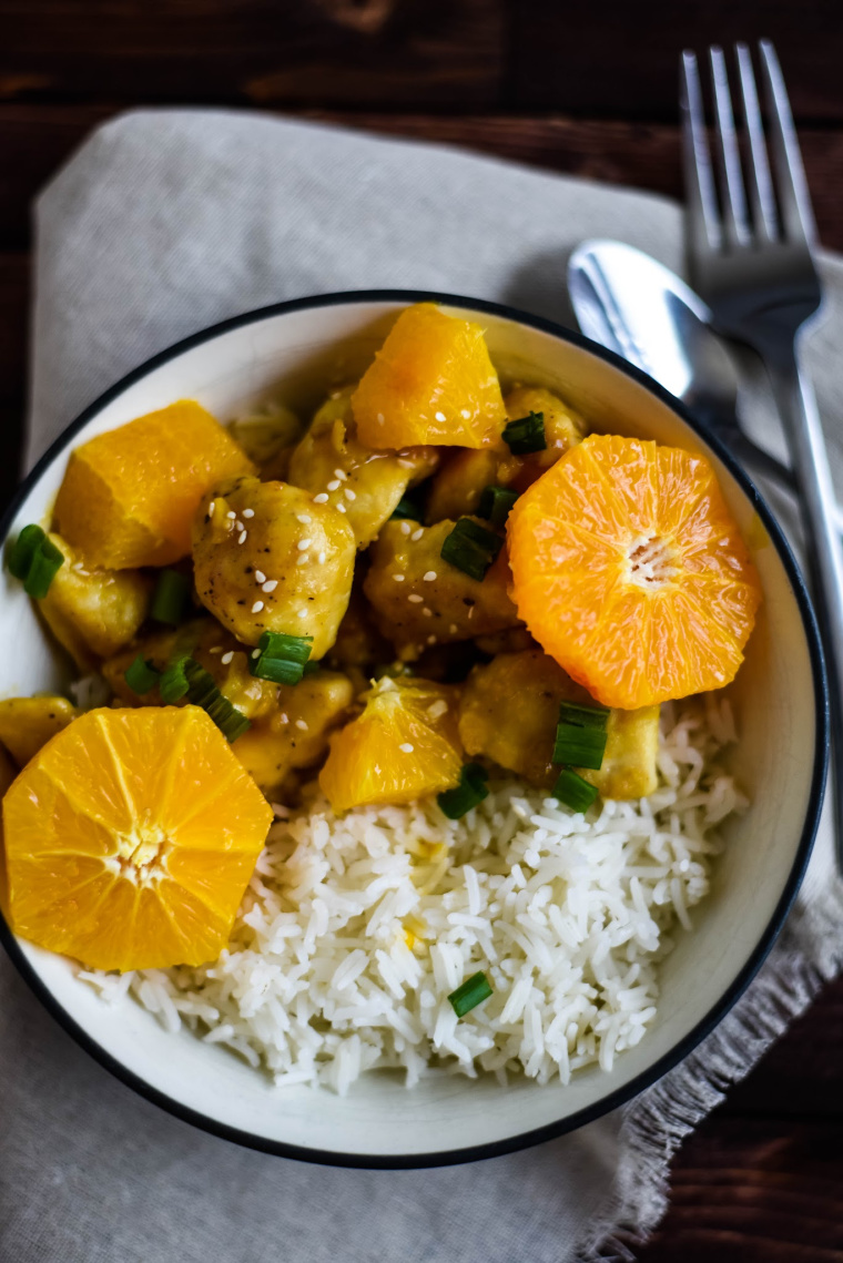 orange chicken in bowl with spoon and napkin