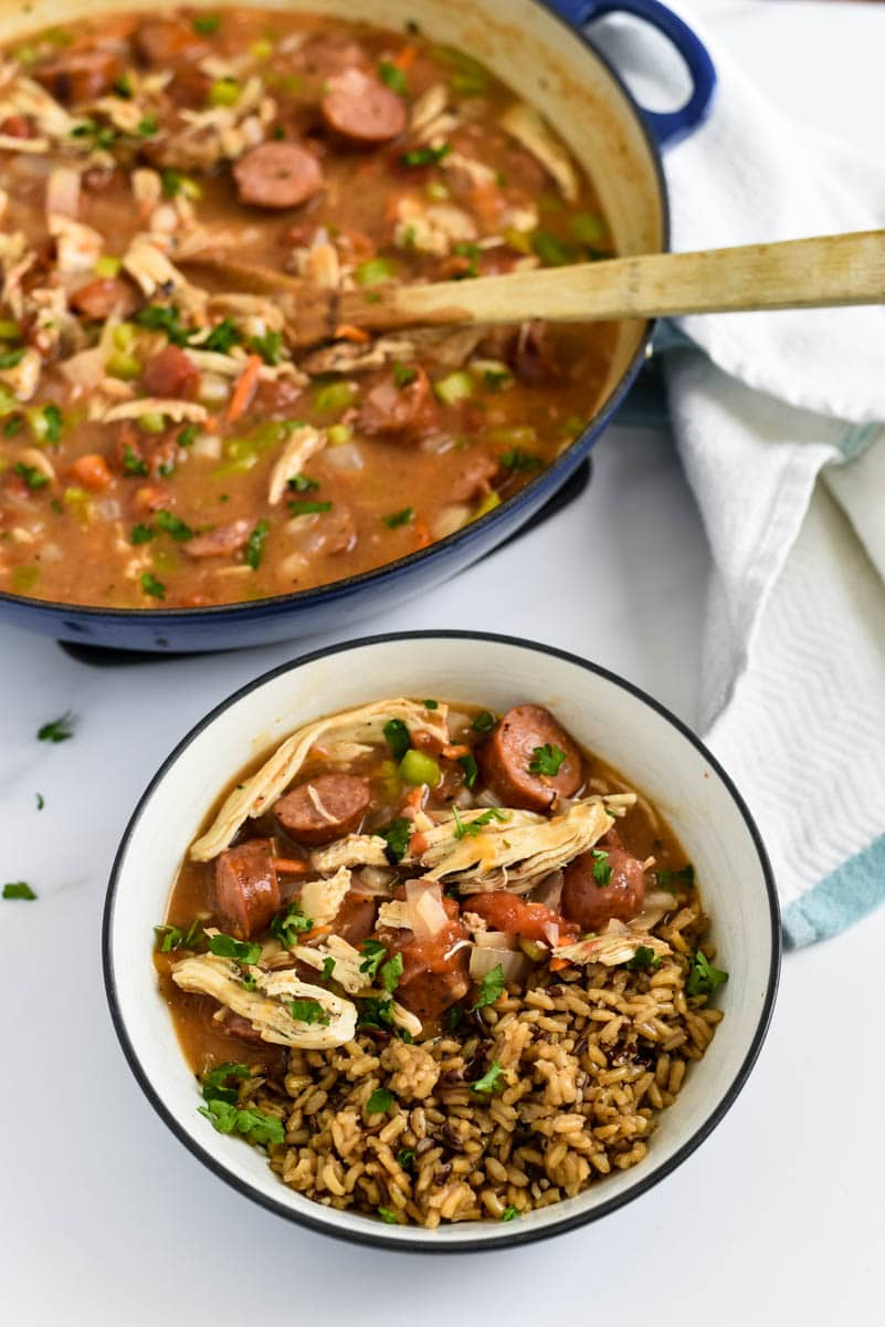 gumbo in bowl with rice next to pot with more gumbo