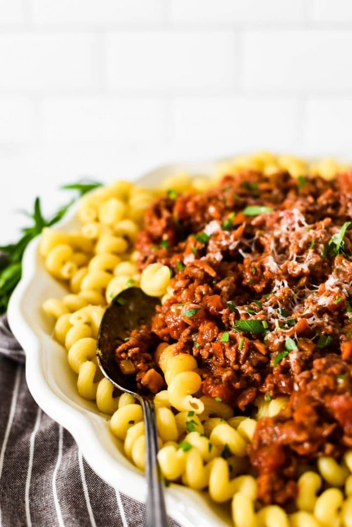 white platter with pasta and beef ragu with serving spoon on the side
