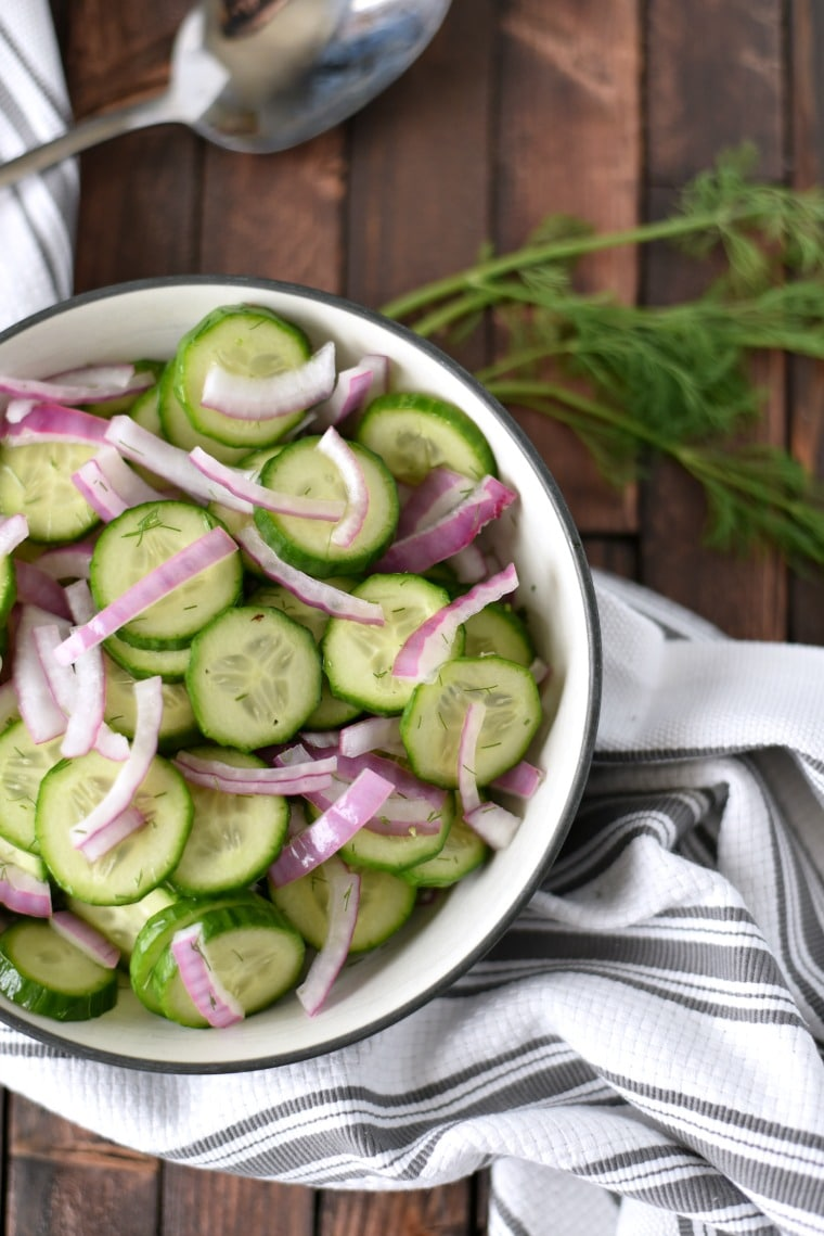 Easy Cucumber Salad in bowl with Spoon and Dill on napkin