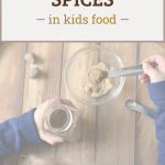 """child's hands measuring spices for baking, with text overlay """"how to add spices in kids food"""""""
