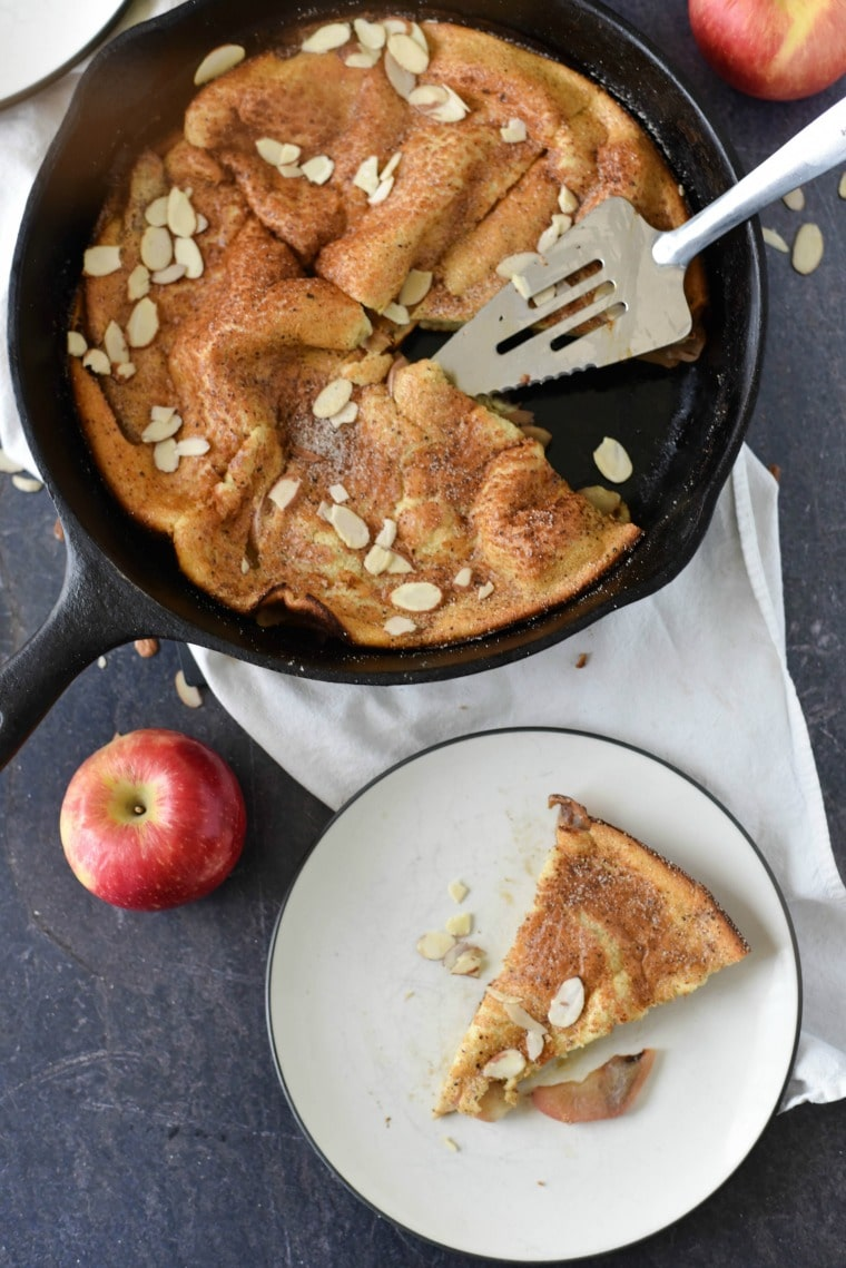A slice of apple spiced dutch baby on a plate next to a cast iron skillet and apples