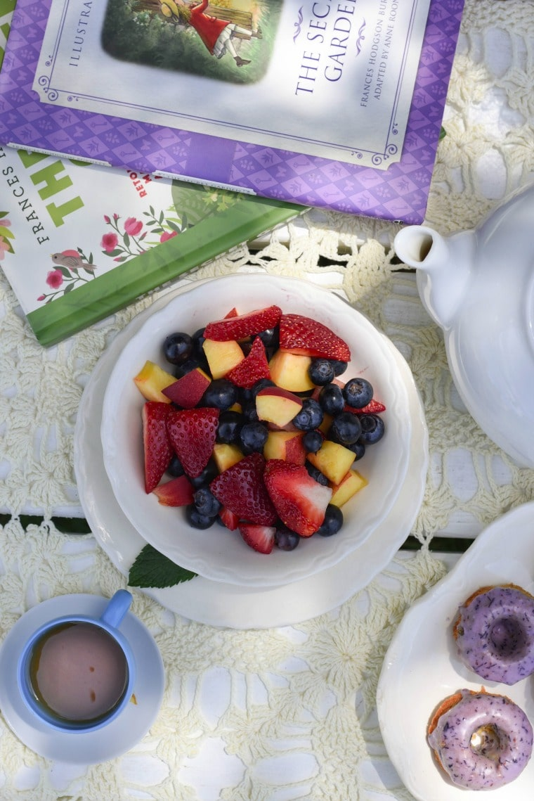 bowl of mixed berries next to tea pot and books