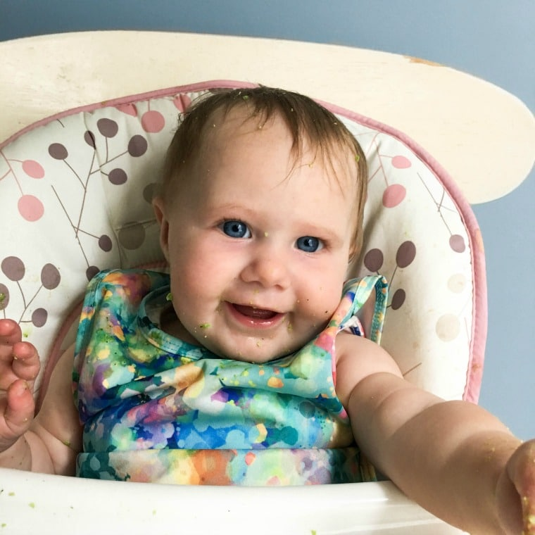 A baby sitting in a high chair smiling