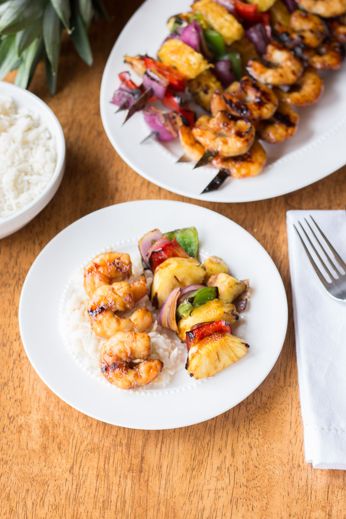 plates on table with rice and shrimp skewers