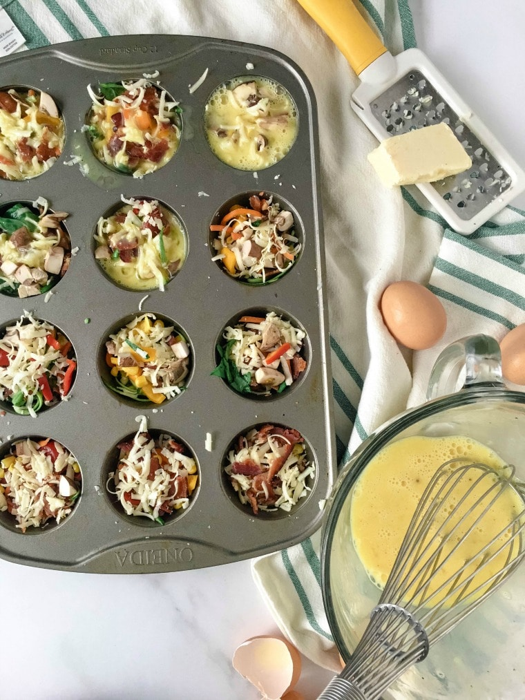 Filling muffin cup with rainbow veggies and eggs