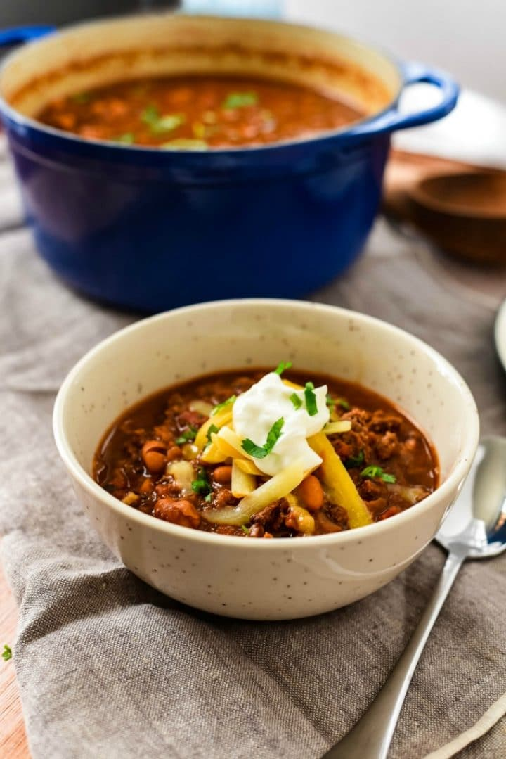 bowl with chili toped with cheese and sour cream