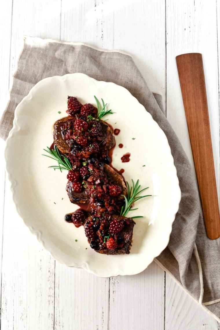 platter with pork chops topped with berry cocoa sauce