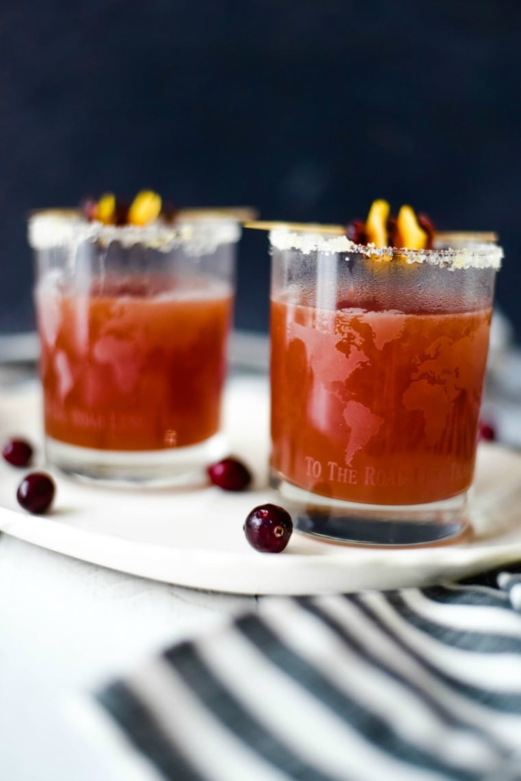 two glasses of cranberry orange cocktails on a plate with cranberries