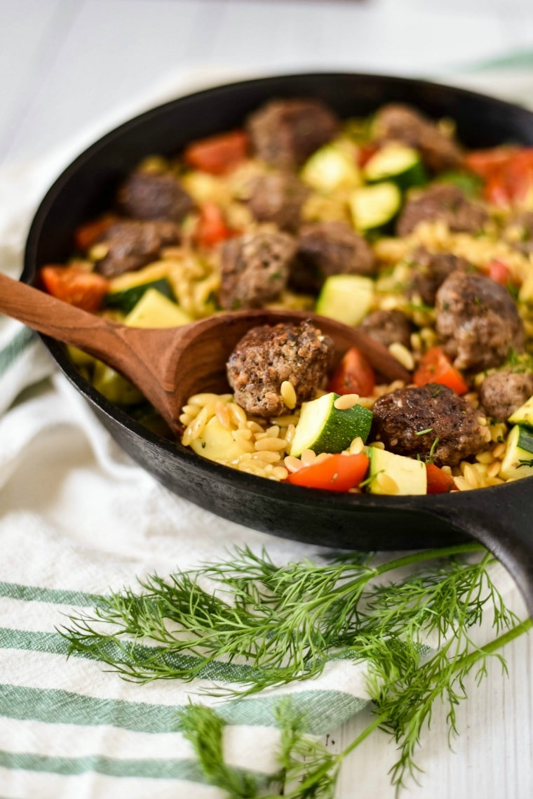 greek meatballs in cast iron skillet with orzo and veggies