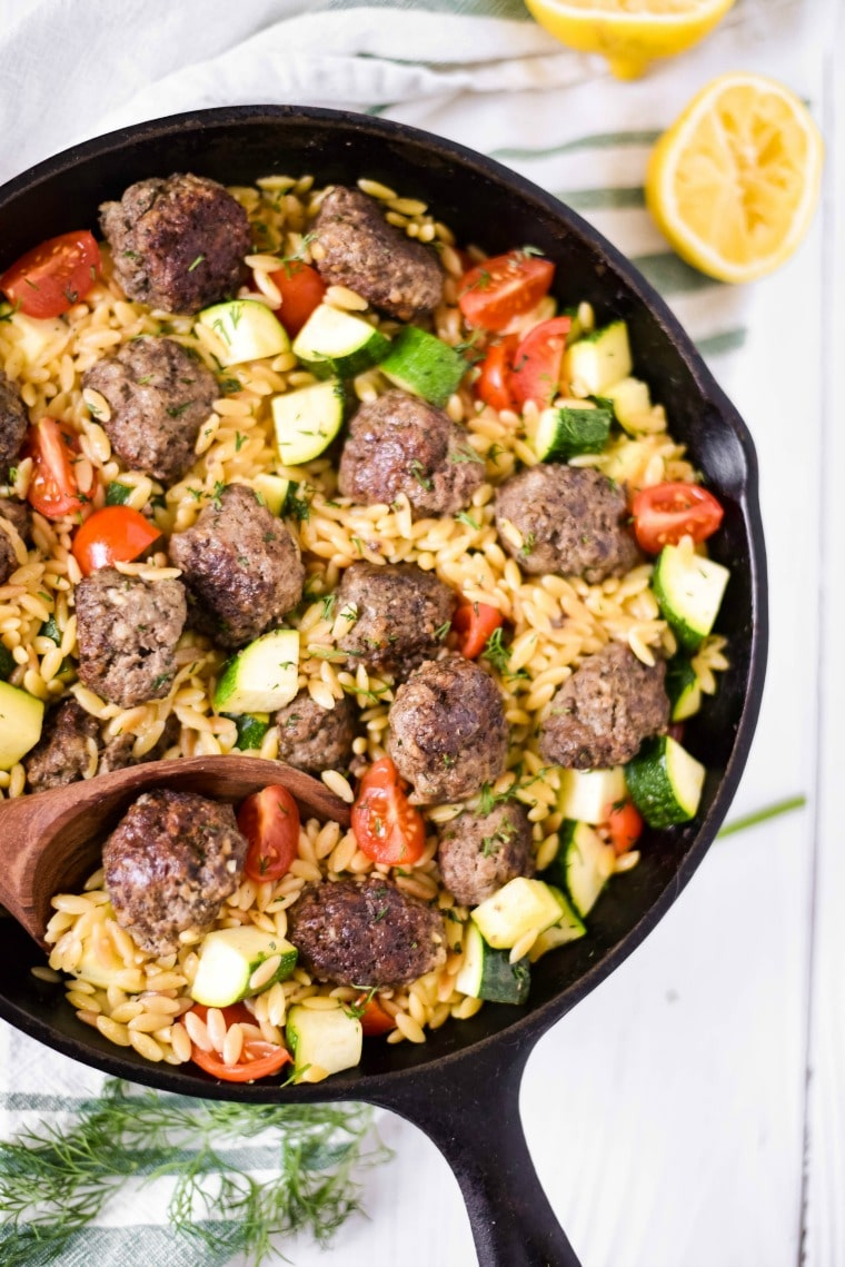 cast iron skillet with meatballs and orzo