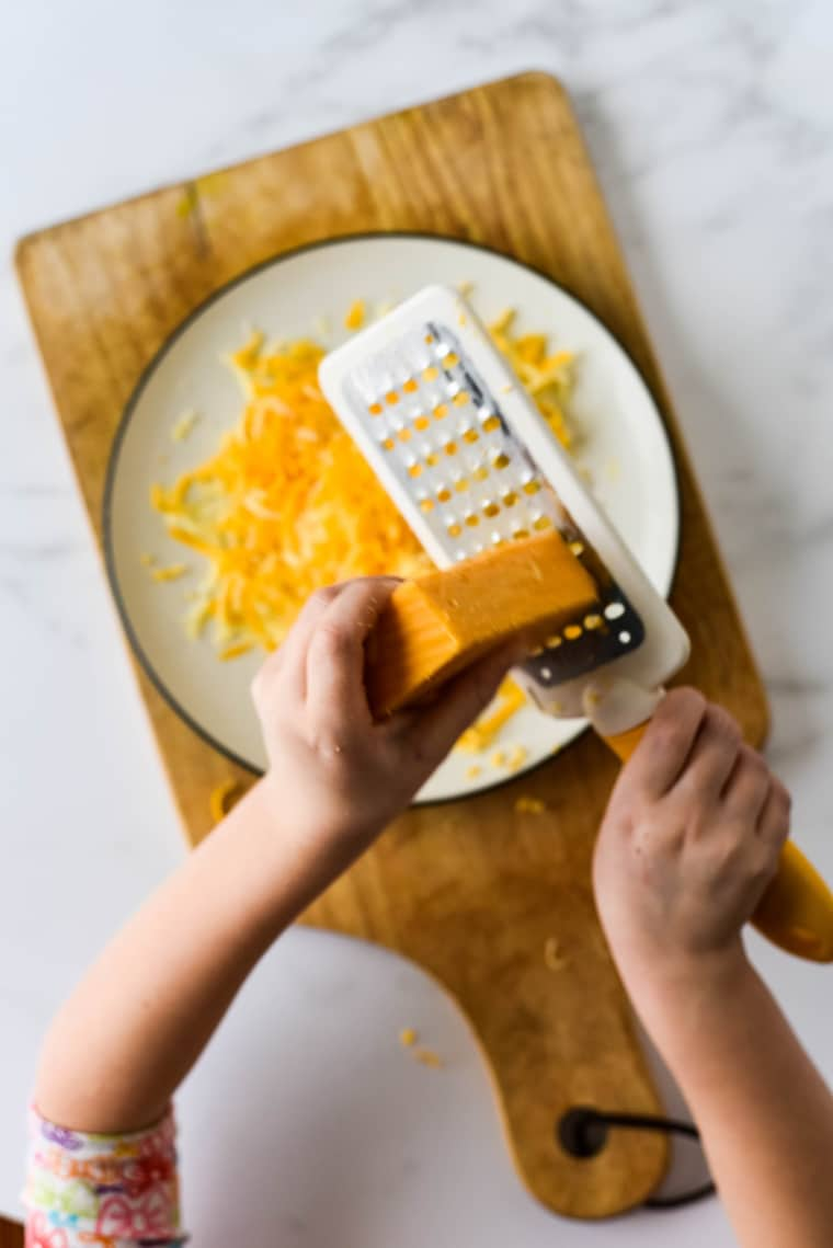 children's hands grating cheddar cheese