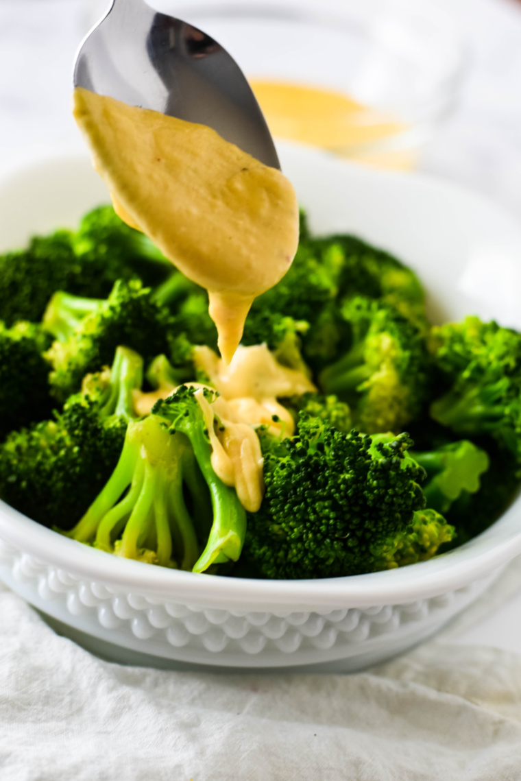 cheese sauce being dribbled on broccoli